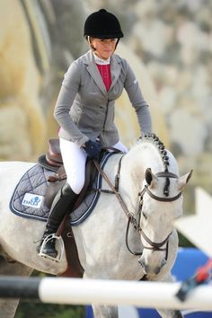 Love the detailing of this coat...Olivia Hamood, the Australian rider, in her grey Animo show-jumping jacket and colored shirt combination, with matching saddle pad!