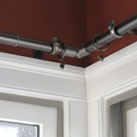 This could be an option to your window conundrum.   Corner adapter installed for corner window treatment