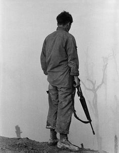 Vietnam War. US Infantryman looks over the fog-shrouded A Shau Valley, a major arm of the Ho Chi Minh Trail. 1969.
