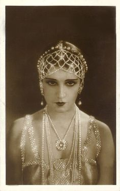 Metallic 1920s headpiece, dress, necklaces. Flapper fashion.