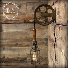 Weve taken an antique cast iron wall mount pulley mechanism and added a wire cage trouble lamp to create a unique vintage industrial light