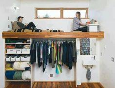 Quarto espaço para cama e para mesinha de estudos em piso superior, acima de armário e pia.