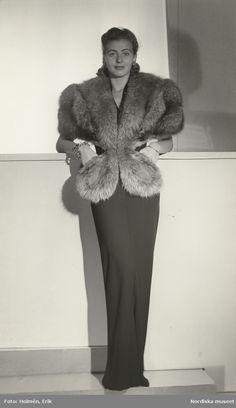 1945. Kvinna i aftonklänning med kortärmad pälsjacka eller boa. Foto: Erik Holmén för Nordiska Kompaniet