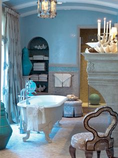 This master bathroom is beachy, blue dream, with blue and green mosaic tiles, glass vases in different shades of blue, a clawfoot tub, a weathered metal pendant light, and a stone tile floor.  The arch of the vaulted ceiling echoes is mirrored in the arched inset shelves.