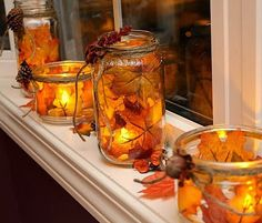 Use fake leaves, jars and LED candles to create a warm glowing fall centerpiece. #DIY