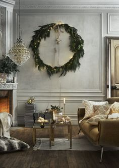 Create a centrepiece in your living room this Christmas by using your decorations more creatively. Here, a large hoop garland with fairy lights creates a spectacular wall display and perfectly complements the neutral decor with gold accents. (Photo: H&M Home)