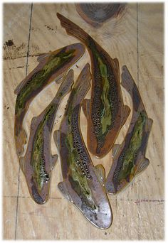 Brown trout shaped ceramic tiles for mosaic. Love this idea for an entryway,