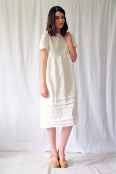 Romantic sundress in pure linen with high neck and pin tuck detailing at the skirt. Mid length. Loose, lightweight, and perfect for a summers day.
