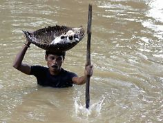 19 Photos Sure to Make You Cry--A resident of Cuttack City, India, saves three kittens during the treacherous floods of 2011