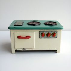 1950s Tin-plate toy stove. Cream & mint green tin metal with red vintage detailing. Small cooker, stove or range for a child or doll.