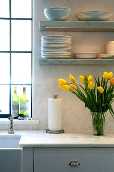 creamy white kitchen cabinets, marble slab countertops & backsplash, marble floating shelves and farmhouse sink.