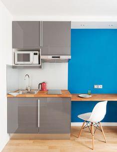 Un estudio de 15 metros cuadrados. la encimera de la cocina se extiende a lo largo de la pared contigua donde hace las veces de barra y de mesa de estudio.