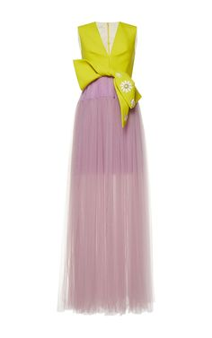 This **Delpozo** gown features a v neckline, a fitted bodice, a bow at the waist, and a full length tulle skirt.