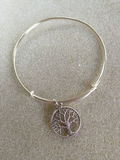 """Simple yet elegant bracelet with a silver-plated """"Tree of Life"""" charm. The bracelet is made of wire coated silver and is non-tarnishing. Alex and Ani Inspired Adjustable Bangle by LeasLOTUSJewelry, $14.00"""