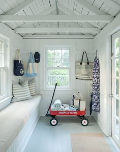 Sweet cottage mudroom features truss ceiling over beadboard walls framing a window over a long built-in bench with beadboard trim