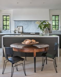 The sleek and elegant kitchen features a 19th Century French walnut dining table and Anziano Chairs by Donghia. Image: Peter Vitale