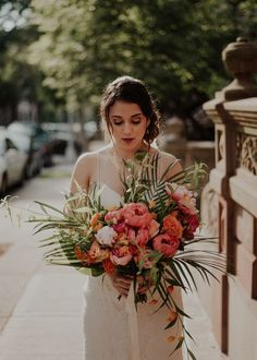 Make peonies tropical for your destination wedding by adding palm and palmetto leaves. Keep the colors vibrant like these orange and pink peonies. This bride completed her look with a loose low bun, red lipstick, and a cami lace wedding dress for a spring or summer wedding. Head to the link for more peony bouquets. // Photo: Wild Sould Studio
