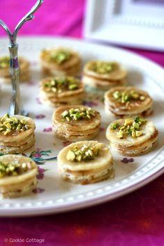 Schaal met zoete hapjes van pannenkoek, roomkaas, honing en pistachenootjes