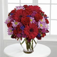 Floral bouquet/arrangement with single red gerbera is surrounded by red roses, lavender button mums, lavender daisies, purple statice, red hypericum and burgundy copper beech leaves in a glass vase. Send #Flowers Online to USA