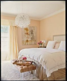 Pale peach walls and drapes instantly soften a bedroom,while a glass chandelier and lucite bench legs help to relfect light. The result is airy and ultra-feminine.