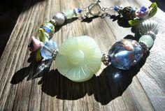 Precízne vyrezaný kvet z polodrahokamu zelený avanturín je doplený o: sýto modrú vinutku s trblietavým zdobením a ružičkou, guličky zeleného avanturínu, veľká kovová guľka, hodvábna ružička, cloissone lienka (ručne maľovaný smalt), tmavo-platinová zvrásnená guľka, obria modrá korálka v tvare cínovky.  Medzi každou korálkou masívny kovový patinový medzikus.  Všetko navlečené na pamäťovom drôte + masívne americké zapínanie Pearl Earrings, Pearls, Jewelry, Art, Art Background, Pearl Studs, Jewlery, Jewerly, Beads