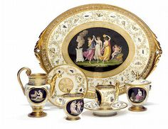 Empire porcelain tête a tête, decorated in colours and gold with cartouches with classical scenery on black ground wreathe with insects and foliage, comprising of; tray, two cups and two saucers, sugar bowl, creamer and coffee pot without cover. Marked Nast a Paris. France c. 1800.  (5)