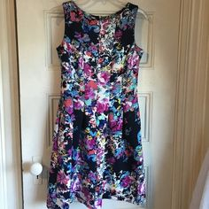 Gabby Skye Floral Dress Floral A-line dress, perfect for summer occasions. Thicker material, exposed zipper in back. Navy blue base with pops of mint green, bright purple, white, yellow, periwinkle blue, and coral. Gabby Skye Dresses Mini