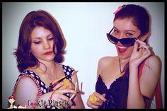 Thany Vieira usando Colar Maçã do Amor, Brinco Cupcake, Anel Gravatinha, Hand Palm Bracelet e Bolsa Shopper. Bianca Christofolletti usando Tiara Catavento, Brinco Cherry, Colar Biscoito, Anel Flower, Anel Flat Cupcake e Bolsa Classic Crossbody.