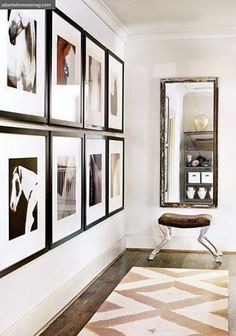 Two rows of black and white custom frames as hallway wall decor and vertical mirror. Love the carved horse leg stool. Simple, neutral and elegant.