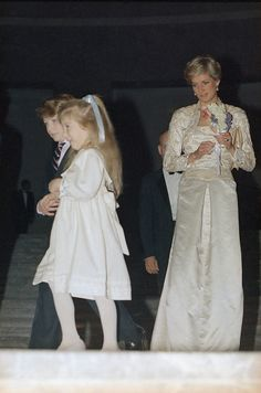 . Carlton, left, and Kyle DeWoody trip away after presenting Princess Diana of Wales with a bouquet in New York on Feb. 2, 1989. The princess, on a two-day visit to New York City, watches the youngsters prior to a dinner at the Wintergarden. (AP Photo/Ron Frehm)