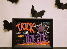 "- This 5x7 black shadow box frame is filled with candy corn, white yarn web in the corner with a purple glitter spider hanging over it and foam bat stickers. Hand painted ""Trick or Treat"" on glass wit"