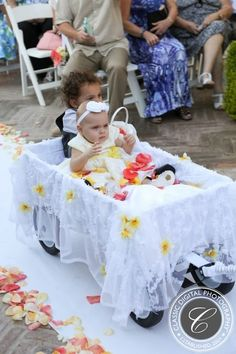 df3f5f76a12 Baby flower girl and ring bearer in decorated white lace wagon with yellow  and pink accents