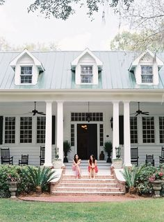 Plantation-style home with wraparound porch, columns and brick-lined stairs.