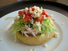 sopes de pollo (chicken sopes) | a gluten-free recipe for thick, fried masa cakes topped with beans, chicken, lettuce, salsa verde, tomatoes and cheese. a mexican restaurant favorite!