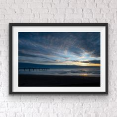 Early morning has the sun peeking out from behind the clouds and the Pier reaching out to the sea. New Brighton, Christchurch, New Zealand