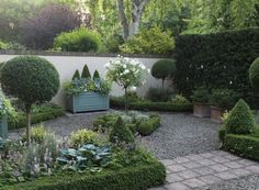 Esme Auers garden, Surrey. Tightly clipped boxwood hedging & topiary, gravel combined with pavers in formal front courtyard.