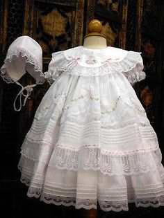So many beautiful details in this darling dress! Classic heirloom dress with white sheer overlay has layers of lace and ruffles for beautiful fullness. Satin pink ribbon inset at the neckline along wi