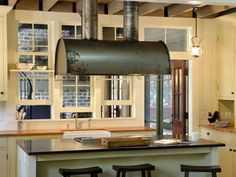 Exposed ceiling beams and an industrial range hood with its oxidation left as is add a casual, country feel to this kitchen by Historical Concepts Architecture & Planning.