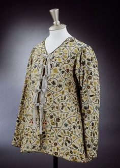 Linen jacket embroidered with silk, silver, and silver gilt thread, English, 1600-1625. Embroidered jackets were popular items of dress for women in the early 17th century. This very simple unlined example represents an informal style. Unlike more fitted versions, this loose, unshaped jacket may have been worn during pregnancy. A repeating pattern of curving scrolls covers the linen from which spring pea pods, oak leaves, acorns, borage, strawberries and honeysuckle embroidered in coloured s...