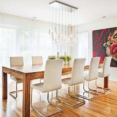 Le décor très aéré de la salle à manger est baigné de lumière naturelle grâce à un rideau plein jour qui couvre un mur complet. La blancheur immaculée des murs laisse la part belle à l'audacieuse peinture réalisée par la propriétaire qui a tiré son inspiration d'une oeuvre de l'artiste-peintre Corno. Avant