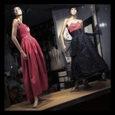 'Deconstructed'. 1950s Frank Usher ball gown shown in two. Coral ball gown left with its hooped and corseted black under dress on right.  #windowdisplay#1950s#ballgown