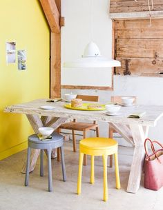 Love these mismatched stools and chairs. Yellow, grey with a hint of pink;  relaxed