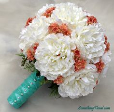 White peony bridal bouquet with delicate coral floral accents, a light base of fern, and an aqua stem wrap accented with pearlsh fern and a silver grey, satin stem wrap and pearls.