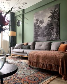 Gray tapestry over a gray sofa, green walls & a beautiful green & clay patterned rug #livingroom
