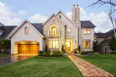 2007 Bellaire new home showcase winner. Stucco & stone exterior, note old English style chimney. Professional landscape with lighting. Wood garage door, reclaimed brick pavers lead to wide glass front door.
