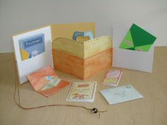 Making travel books with children - ONE HEART ARTS.  Suitcase book--accordion book with pockets and added cover and string-closure. Two center sections are cut in shape of suitcase. Mini-books inside the pockets tell the story of a journey (wallet, passport, journal, menu, letter home, tourist brochure)