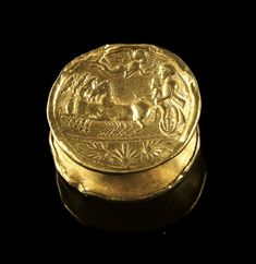 Golden spool with concentric circles on one side and a quadriga with two charioteers and a nike who is crowning one ot them. 2nd half 3rd century B.C.