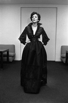 Model is wearing a black belted gown with an upturned collar from the Bill Blass Spring/Summer Ready to Wear 1973