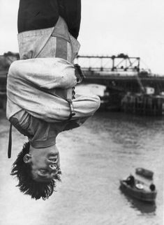 Escapologist Timothy Dill-Russell, adviser to the musical 'Man of Magic' about Houdini, is strapped in a straight-jacket as he hangs upside down over the Thames before his attempt at escape, 1966
