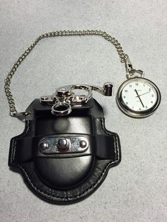 Very cool-looking pocket watch with a black leather pouch. Pouch connects to a…